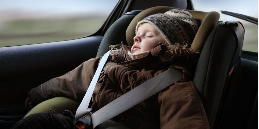 child wearing puffy coat in car while strapped in car seat