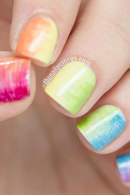 You'll need a super-skinny, flat nail art brush to achieve this rainbow blur — moving the brush horizontally across the nail pushes two nail polish hues into each other, blending them seamlessly. See more at The Nailasaurus »