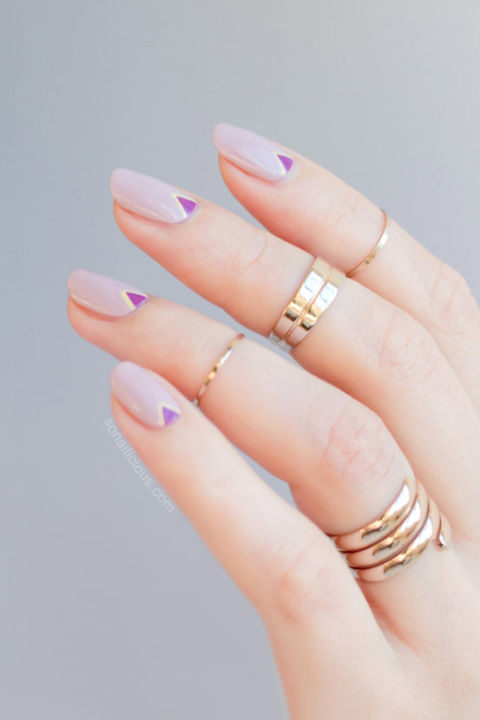 A pretty lilac nail gets a hint of geometric edge thanks to micro-triangles in a deeper royal hue. See more at So Nailicious »