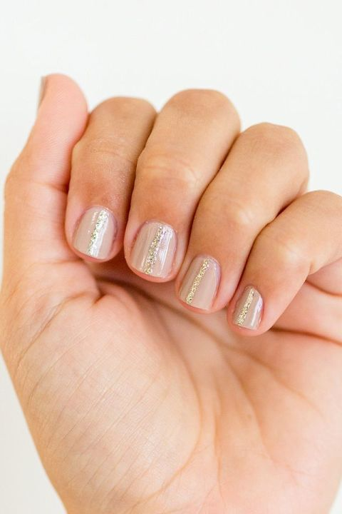 "Want a simple way to upgrade your favorite Essie ""Topless and Barefoot"" nude? Draw a skinny line of gold glitter down the center of each nail and watch how pretty the metallic looks glinting in the summer sun.  See more at Lauren Conrad »"