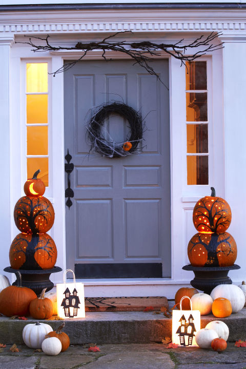 Deck out the front door with a pair of pumpkin pillars. Paint on gnarled trees, and then use a drill to create a constellation of stars. For a third tier, cut out a crescent moon on a mini pumpkin.