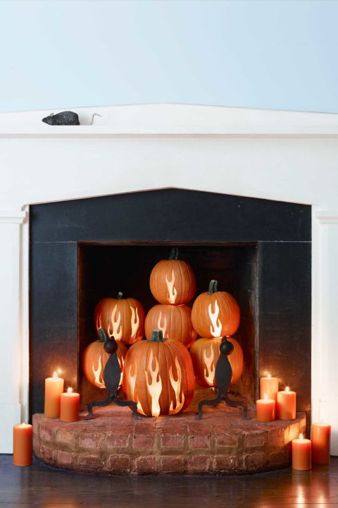 Set the scene with a whole pumpkin tableau. Avoid any real fires by opting for flameless illumination instead. 