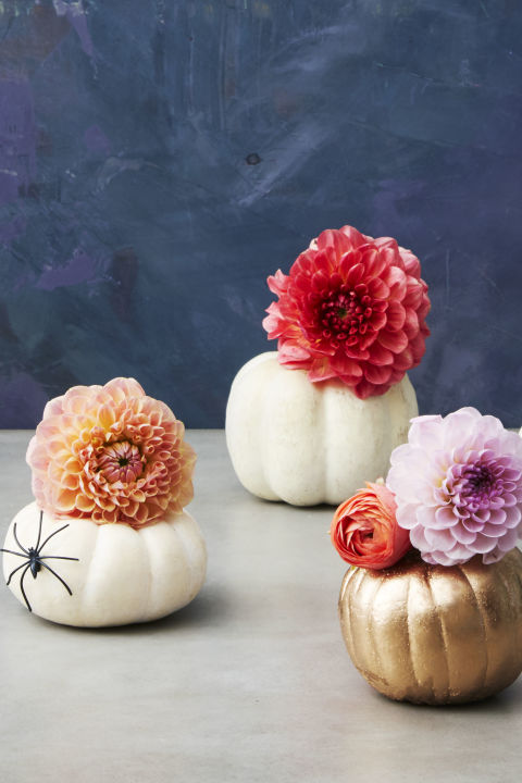 Carve the top off a mini pumpkin, then cut the bottom off a water bottle and drop it in to act as a vase. We filled ours with ranunculuses, mums and dahlias.What you'll need: gold paint ($2, amazon.com), plastic spiders ($6, amazon.com)