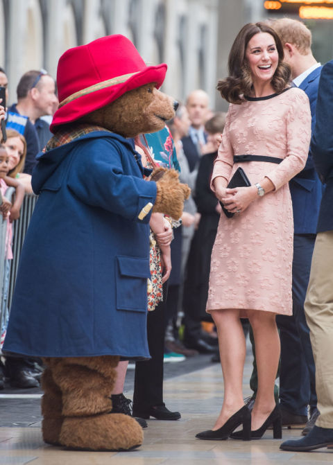 October 16, 2017&amp;nbsp;&mdash; Kate Middleton met Paddington Bear at his namesake train station in London while wearing a knee-length pink dress by Orla Kiely&amp;nbsp;with a black bow at the waist to set off her just-now visible&amp;nbsp;baby bump.