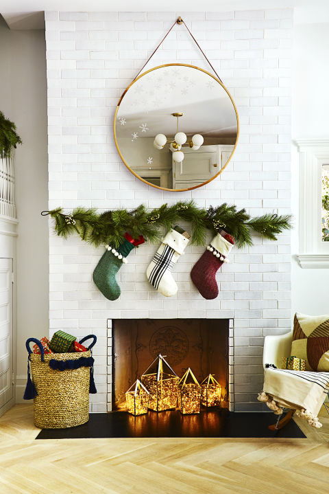 Use a washable-paint marker to add fluttery flakes to a mirror. Festive stockings — attached to a faux garland — and a tassel basket hold plenty of goodies.