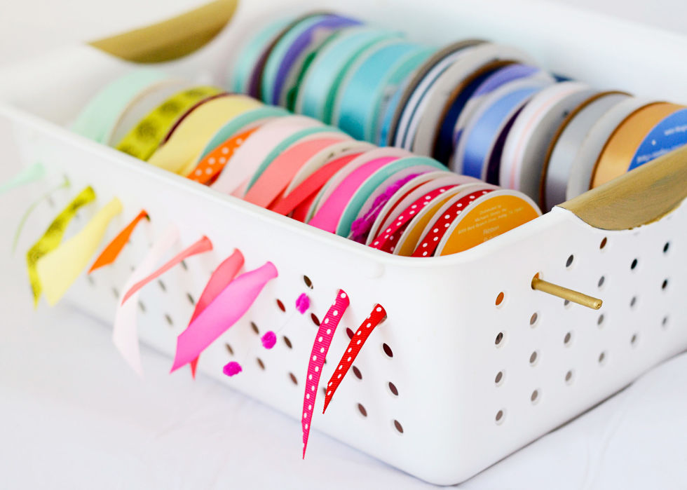 """My ribbon holder saves me from digging when I'm sewing. Slide spools onto a 14 1/2 inch thin wooden dowel, fit the stick across a slotted plastic bin's top row of holes, and pull ribbon ends through the sides. Repeat with as many rolls as your bin can hold."" –Halsey Bishop of Spunky Junky"