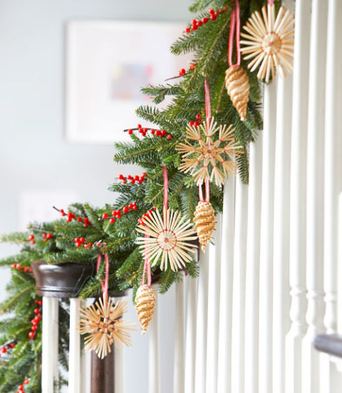 If there are too many ornaments for the tree, add the extras to an evergreen garland. Drape greenery along a doorway or bannister, then hang ornaments from ribbon loops and insert berry branches for pops of color.