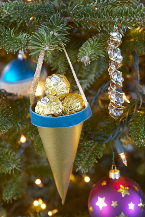 Paper cones filled with candy work as ornaments now and party favors later. Try wrapped peppermints, chocolate kisses or truffles for more color than mess. Get the tutorial » What you'll need: gold origami paper ($8 for 100, amazon.com), velvet ribbon ($12, amazon.com)